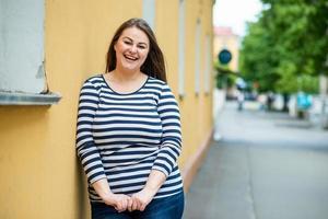 Sonriente mujer hermosa plus size mirando directamente a la cámara en la calle sobre fondo naranja foto