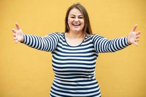 sonriente, linda mujer con los brazos abiertos sobre fondo naranja foto