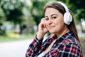 Woman in headphones on a background of the city, cute smiling photo