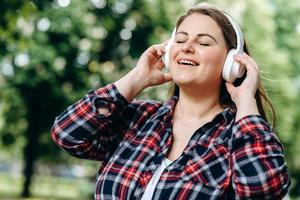 Cheerful woman in wireless headphones singing her favorite song photo