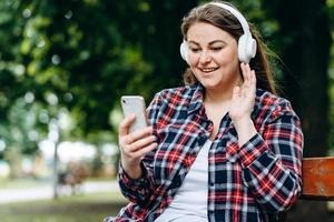 Beautiful, charming woman in earmuffs, sitting on a bench, listening to something in headphones, holding a smartphone photo