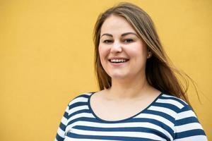 Feliz mujer con sobrepeso posando aislado sobre fondo naranja foto