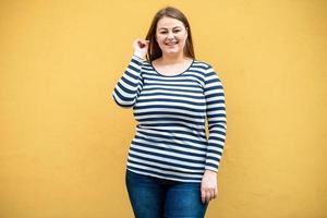 Mujer con sobrepeso en un suéter de rayas posando en el fondo de una pared naranja foto