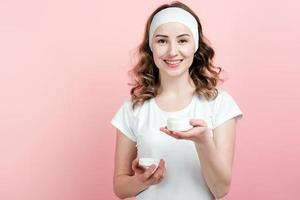 Happy girl with a bandage on her head holds in hand a jar of moisturizer photo