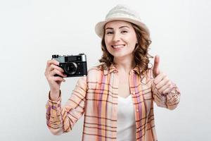 chica guapa con sombrero y retrocamera en manos está satisfecha con su trabajo, mostrando el pulgar hacia arriba. foto