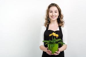 Beautiful, smiling girl holds a flowerpot in her hands, posing in studio on a white wall background photo