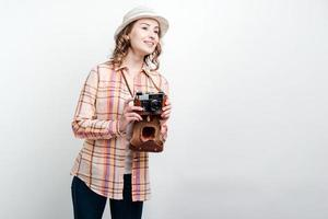 Girl with retro camera and wearing hat looks away on white wall background photo