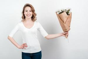 Cute short haired girl in white blank t-shirt holding a bouquet of colorful flowers, smiling broadly standing over white background. photo