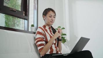 Young woman on the couch on a video call with a laptop