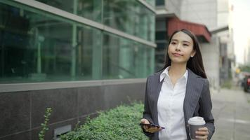 Asian businesswoman walking in the street while using a smartphone and holding a coffee cup video