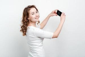 Blonde woman   standing against a studio background holding a smartphone and smile to camera photo