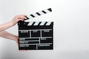 Movie production clapper board in the female hands against a white background photo