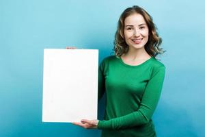 Young beautiful woman holding white object on her hand on blue background photo