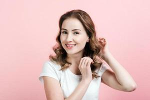 Indoor portrait of excited curly woman . Young lady smiling on pink background. photo