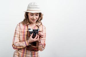 Retrato de una niña feliz con sombrero con cámara retro sobre fondo blanco de estudio foto