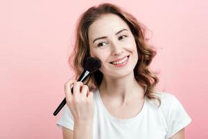 beautiful woman applies blush with a brush. Make up photo