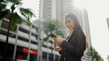 Empresaria asiática caminando en la calle mientras usa un teléfono inteligente y sostiene una taza de café video