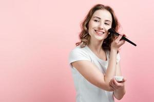 Smiling beautiful girl in white t-shirt powder face, on pink background. photo