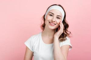Smiling girl posing with headband. Isolated on pink background. photo