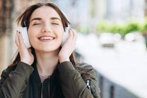 Happy, young girl enjoys the music coming from the headphones. photo