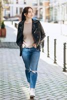 chica caminando por la calle, vistiendo una chaqueta de cuero fresca foto