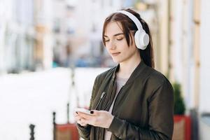 Close-up portrait of nice attractive cute adorable cheerful girl in headphones looking at something on the phone photo
