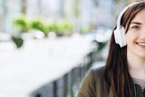 Young woman wearing headphones with a happy face standing in middle of street photo