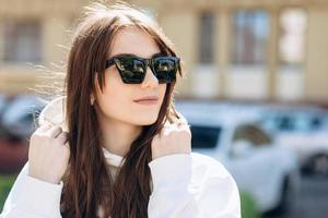Cute, attractive brunette posing in sunglasses and a white hooded sweater photo