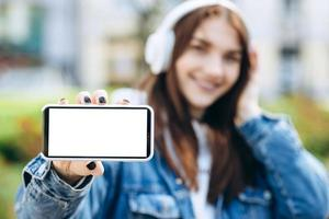 Close-up view of a girl in headphones on a blurred background shows a white phone screen, copy space photo