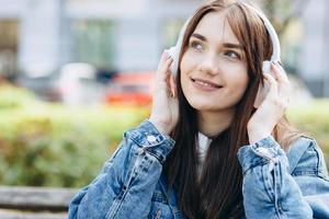 Attractive, young woman, against the backdrop of the city, listening to music, looking at something, enjoying music photo