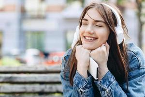 Young, smiling woman listening music with headphones. Girl listening songs via wireless headphones. Closeup face of teen. photo