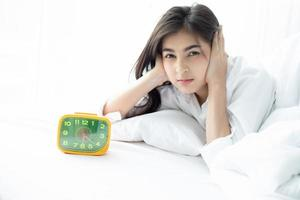 Asian woman hates waking up early in the morning. Sleepy girl looking at alarm clock and trying to hide under the pillow photo