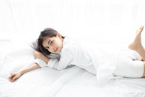 Asian woman Beautiful young smiling woman sitting on bed and stretching in the morning at bedroom after waking up in her bed fully rested and open the curtains in the morning to get fresh air. photo