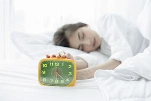 asian woman happy waking up and turning off the alarm clock having a good day photo