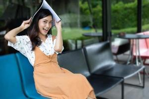 Asian women reading and smiling and happy Relaxing in a coffee shop after working in a successful office. photo