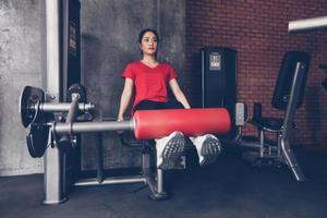 beautiful muscular fit woman exercising building muscles and fitness woman doing exercises in the gym. Fitness - concept of healthy lifestyle photo