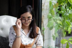 Asian women are holding glasses and smiling at a coffee shop on a holiday. photo