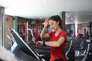 Asian women running sport shoes at the gym while a young caucasian woman is having jogging on the treadmill photo