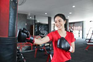 Beautiful women asian boxer happy and fun fitness boxing and Punching A Bag With wearing boxing gloves. photo