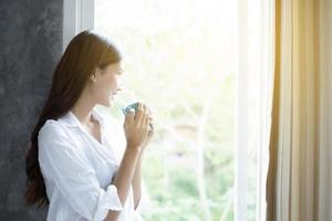 mujeres asiáticas tomando café y se despiertan en su cama completamente descansadas y abren las cortinas por la mañana para tomar aire fresco bajo el sol foto