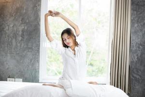 mujer asiática hermosa joven mujer sonriente sentada en la cama y estirándose por la mañana en el dormitorio después de despertarse en su cama completamente descansada y abrir las cortinas por la mañana para tomar aire fresco. foto