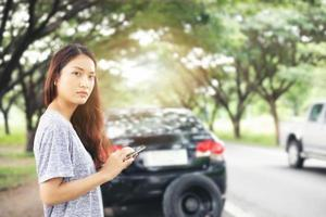 Asian woman using mobile phone while looking and Stressed man sitting after a car breakdown on street photo