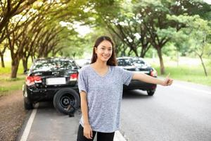 Stressed women  after a car breakdown with Red triangle of a car on the road photo