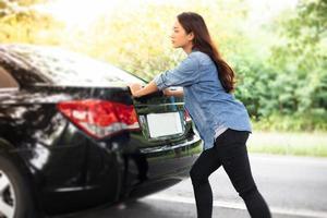 mujeres estresadas después de una avería de coche con triángulo rojo de un coche en la carretera foto