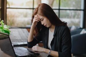 empresaria asiática seria sobre el trabajo realizado hasta el dolor de cabeza foto
