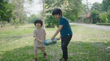 Two kids carry out scraps of fruits and vegetables to learn how to make natural compost video