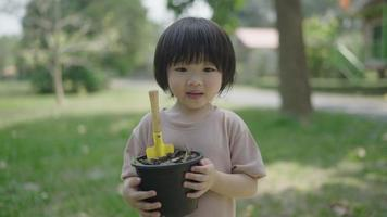 An Asian boy holds a pot with compost and a hoe to plow the soil to learn how to make natural compost. video