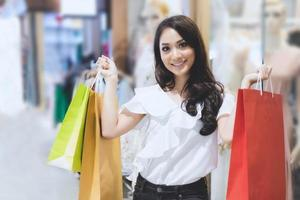 Asian women and Beautiful girl is holding shopping bags smiling while doing shopping in the supermarket photo