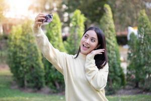 Las mujeres asiáticas sonríen felices tomando fotos y selfie en tiempo de relajación