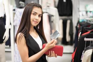 Sonriente joven asiática con compras y compra con tarjeta de crédito en el centro comercial foto
